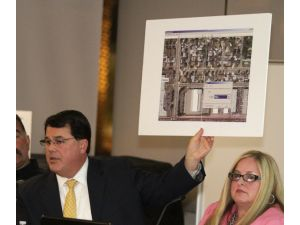 Supervisor Shawn Nelson holds up an aerial view of the site for a proposed homeless shelter during a public meeting at the Fullerton Library in March.