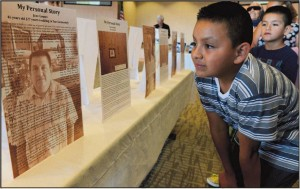 Dionisio Gomez, 10, and his brother Allan, 7, look at their father's biography in an exhibit at Our Lady of Fatima Catholic Church on generations of families who migrated from El Bajio, Mexico, to San Clemente. About 1,500 of San Clemente's 64,000 residents can be traced to this multigenerational migration.