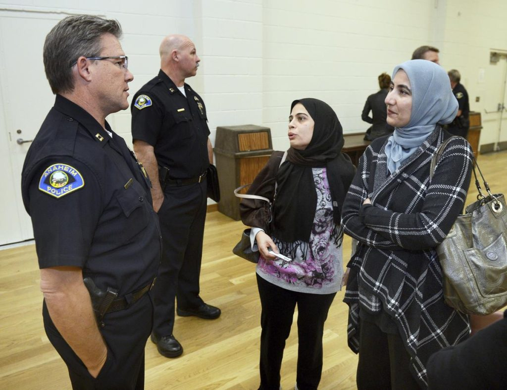 Anaheim Police Captain Eric Carter talks with Uzma Ali and Nasreem Patel at a community meeting in the Brookhurst Community Center Wednesday.  Carter is the department's community services commander. ///ADDITIONAL INFORMATION: 12/9/15 - anaheim.muslims.12.10.15 - BILL ALKOFER, STAFF PHOTOGRAPHER -  Anaheim Police Chief Raul Quezada hosted a meeting Wednesday at the Brookhurst Community Center to show committment from his department against racist attacts against the Muslim Community.